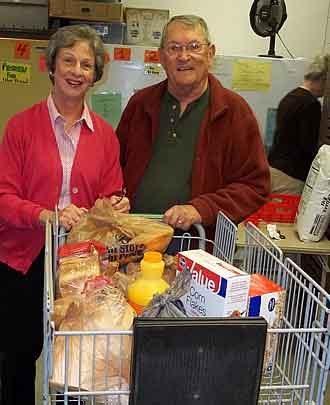 Two volunteers pushing a cart of groceries.