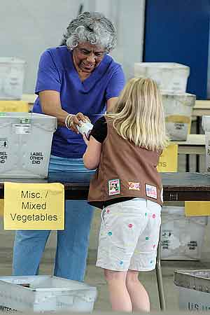 Young girl and older woman organizing canned food.